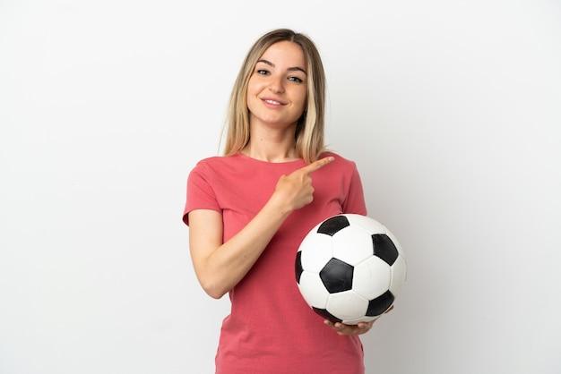 Junge fußballspielerfrau über isolierter weißer wand, die auf die seite zeigt, um ein produkt zu präsentieren