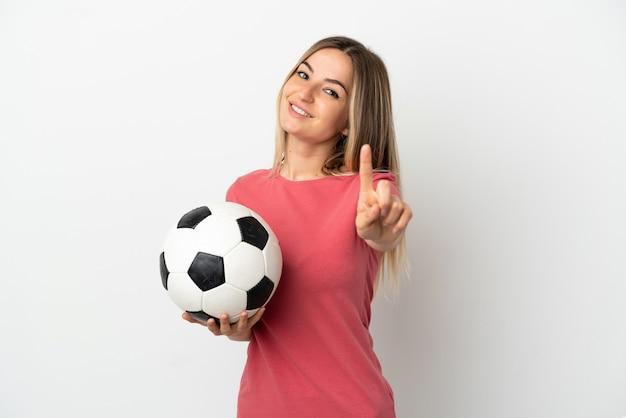 Junge fußballspielerfrau über isolierter weißer wand, die einen finger zeigt und hebt