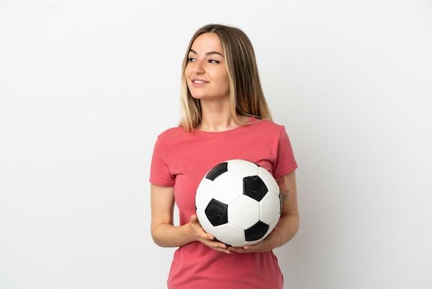 Junge fußballspielerfrau über isolierter weißer wand, die zur seite schaut und lächelt
