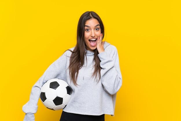 Junge fußballspielerfrau über lokalisierter gelber wand mit überraschung und entsetztem gesichtsausdruck