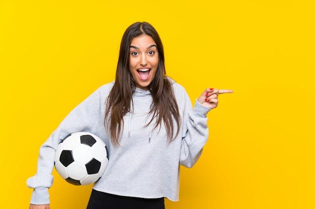 Junge fußballspielerfrau über lokalisierter gelber wand überraschte und finger auf die seite zeigend