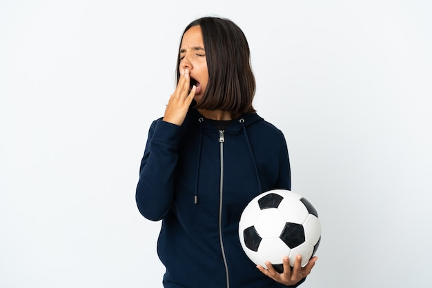 Junge fußballspielerin frau lokalisiert auf weißem gähnen und kegeln weit geöffneten mund mit hand