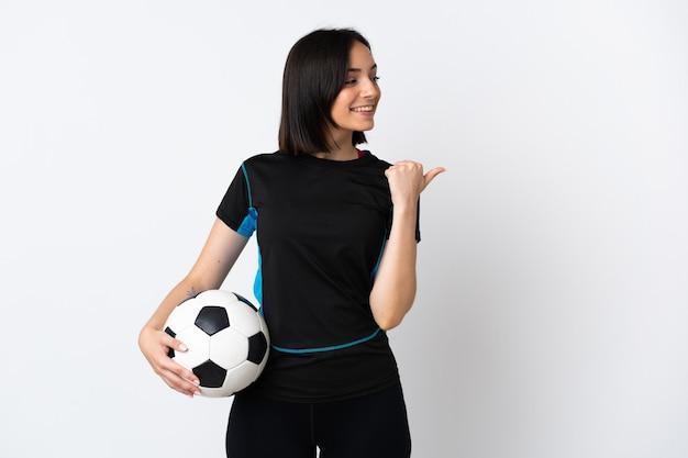 Junge fußballspielerin isoliert auf weißem hintergrund, die auf die seite zeigt, um ein produkt zu präsentieren