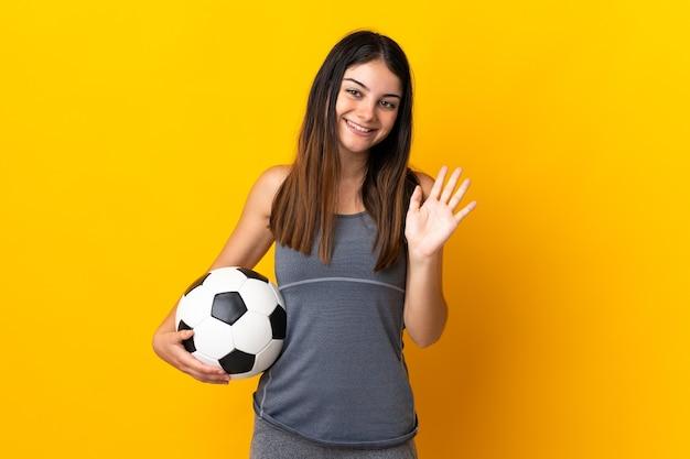 Junge fußballspielerin lokalisiert auf gelbem gruß mit hand mit glücklichem ausdruck
