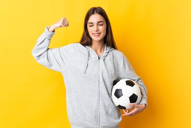 Junge fußballspielerin lokalisiert auf gelbem hintergrund, der starke geste tut