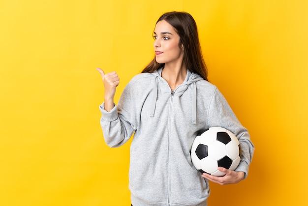 Junge fußballspielerin lokalisiert auf gelbem hintergrund, der zur seite zeigt, um ein produkt zu präsentieren