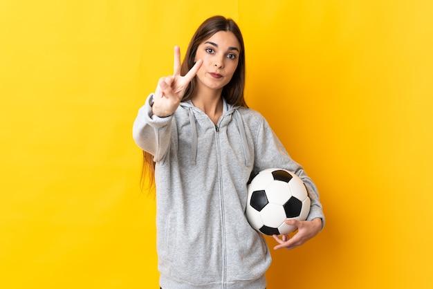 Junge fußballspielerin lokalisiert auf gelbem hintergrund lächelnd und siegeszeichen zeigend