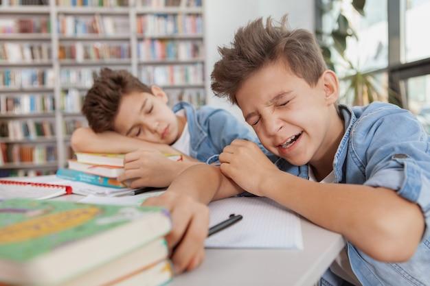 Junge gähnt und fällt in die bibliothek, nachdem er bei seinem zwillingsbruder studiert hat