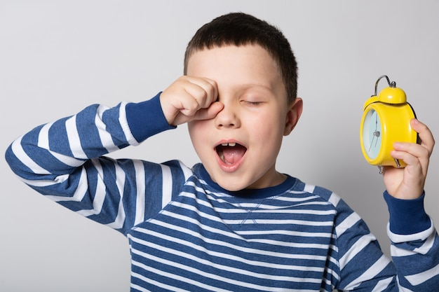 Junge gähnt und hält in der hand einen gelben wecker auf weißem hintergrund