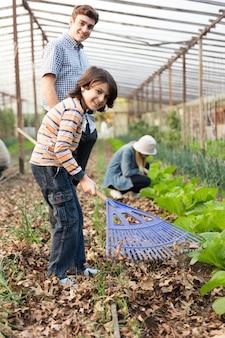 Junge gärtner im gewächshaus, die spaß haben