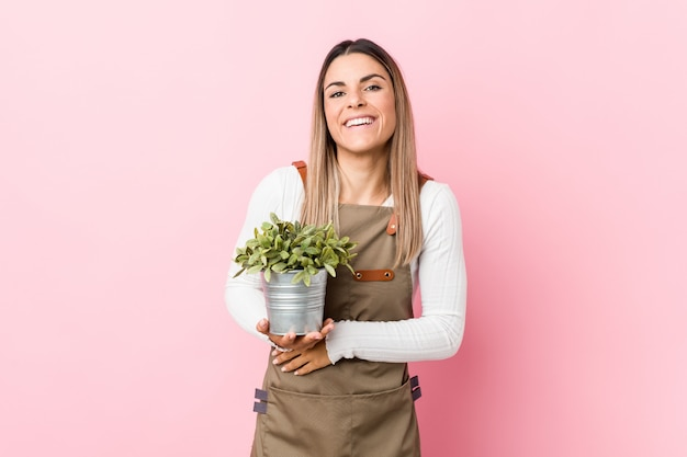 Junge gärtnerfrau, die eine anlage lacht und spaß hat hält.