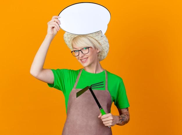 Junge gärtnerfrau mit den kurzen haaren in der schürze und im hut, die mattock und leere sprachblasenzeichen über kopf halten und kamera betrachten, die mit glücklichem gesicht über orange hintergrund steht