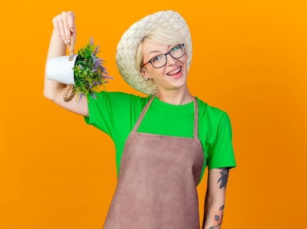 Junge gärtnerfrau mit den kurzen haaren in der schürze und im hut, die topfpflanze betrachten, die kamera lächelnd mit glücklichem gesicht steht über orange hintergrund