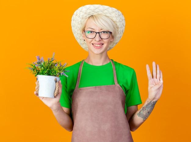 Junge gärtnerfrau mit den kurzen haaren in der schürze und im hut, die topfpflanze betrachten, die kamera lächelnd mit glücklichem gesicht zeigt, das nummer vier über orange hintergrund steht