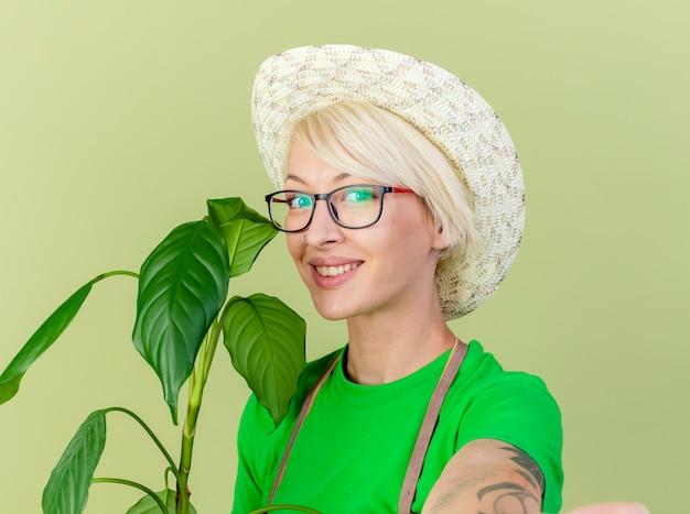 Junge gärtnerfrau mit den kurzen haaren in der schürze und in der hut-haltepflanze, die kamera mit lächeln auf gesicht betrachtet, das über hellem hintergrund steht
