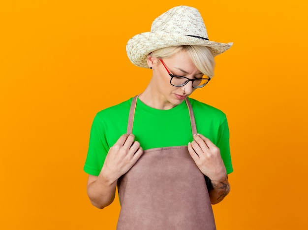 Junge gärtnerfrau mit kurzen haaren in der schürze und im hut, die hände auf brust halten, die unten mit traurigem ausdruck stehen, der über orange hintergrund steht