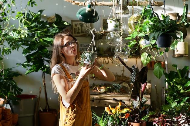 Junge gärtnerin arbeitet mit zimmerpflanzen blumenladen geschäftsinhaber mit kleinen blumentopf holding