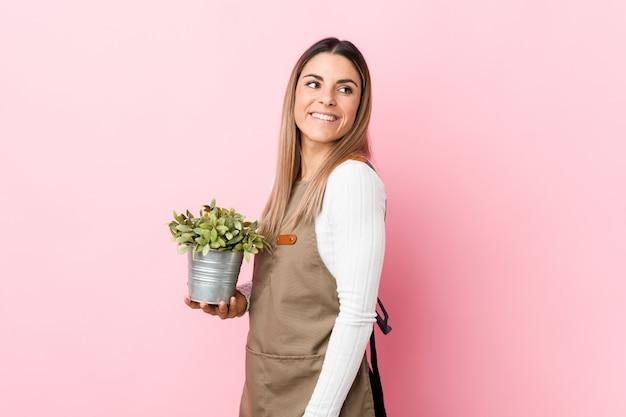 Junge gärtnerin, die eine pflanze hält, schaut lächelnd, fröhlich und angenehm beiseite.