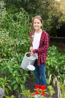 Junge gärtnerin, die gartenbett mit reifem gemüse gießt