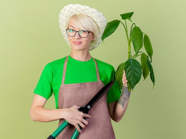 Junge gärtnerin mit kurzen haaren in der schürze und im hut, die pflanze und heckenscheren halten, die kamera mit lächeln auf gesicht betrachten, das über hellem hintergrund steht