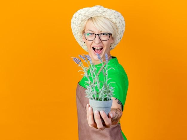 Junge gärtnerin mit kurzen haaren in schürze und hut, die eine topfpflanze zeigt, die mit glücklichem gesicht auf orangefarbenem hintergrund lächelt