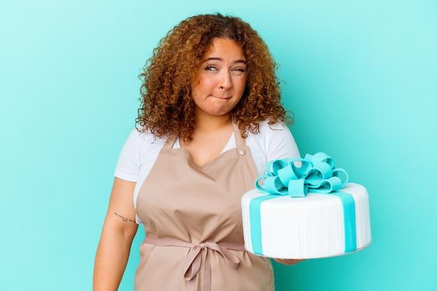 Junge gebäcklateinfrau, die einen kuchen lokalisiert auf blauem hintergrund verwirrt hält, fühlt sich zweifelhaft und unsicher.