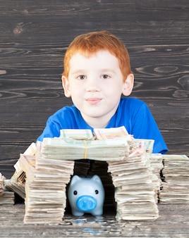Junge gebaut für sein blaues sparschwein mit münzen haus von packungen papiergeld, nahaufnahme