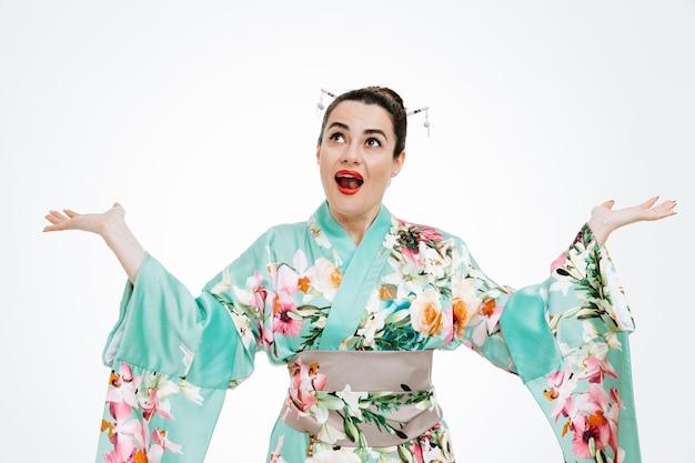 Junge geisha-frau im traditionellen japanischen kimono, die glücklich und überrascht aufschaut und die arme hebt, die über der weißen wand stehen?