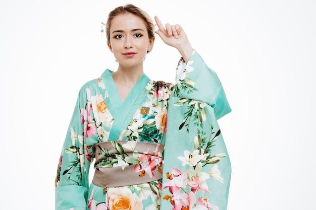 Junge geisha-frau im traditionellen japanischen kimono, die mit einem lächeln auf dem intelligenten gesicht nach vorne schaut und mit dem zeigefinger auf die weiße wand zeigt