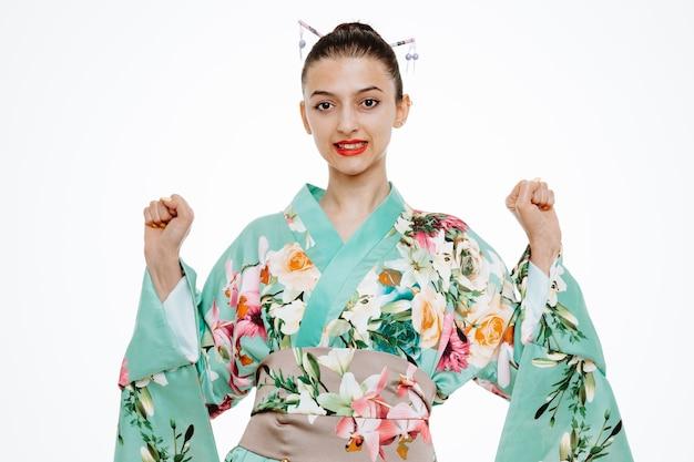 Junge geisha-frau im traditionellen japanischen kimono, die mit ernstem, selbstbewusstem ausdruck nach vorne schaut und die fäuste über der weißen wand hebt