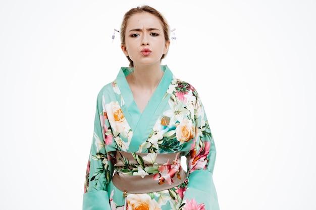 Junge geisha-frau im traditionellen japanischen kimono, die mit stirnrunzelndem gesicht auf die weiße wand blickt