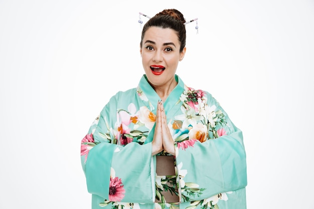 Junge geisha-frau im traditionellen japanischen kimono, die nach vorne schaut und lächelnd die hände zusammenhält in der grußgeste, die über der weißen wand steht?