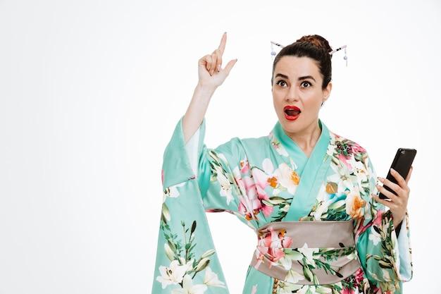Junge geisha-frau im traditionellen japanischen kimono, die smartphone hält und nach vorne schaut, überrascht mit einem lächeln auf einem intelligenten gesicht, das mit dem zeigefinger nach oben zeigt, eine gute idee