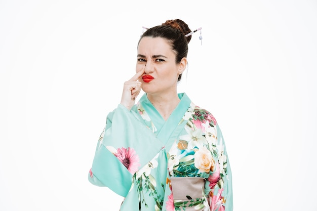 Junge geisha-frau im traditionellen japanischen kimono, die verwirrt nach vorne schaut und ihre nase berührt, die über der weißen wand steht?