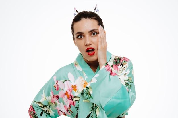 Junge geisha-frau im traditionellen japanischen kimono erstaunt und überrascht, die hand auf ihrer wange auf weiß haltend