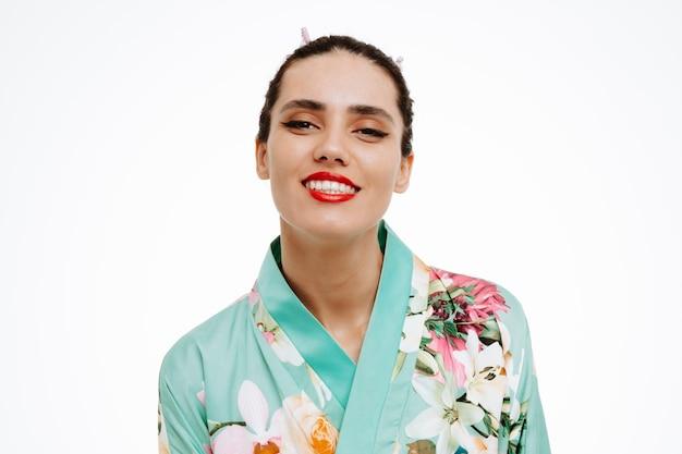 Junge geisha-frau im traditionellen japanischen kimono glücklich und erfreut breit lächelnd auf weiß