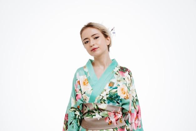 Junge geisha-frau im traditionellen japanischen kimono mit blick auf die vorderseite glücklich und positiv lächelnd selbstbewusst über weißer wand stehend