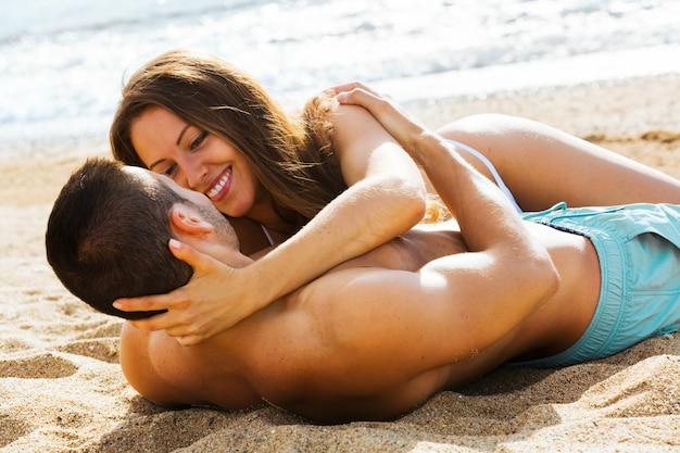 Junge geliebte, die am sandigen strand datum haben