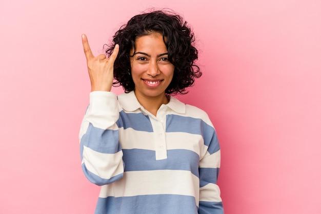 Junge gelockte lateinische frau lokalisiert auf rosa hintergrund, der felsengeste mit den fingern zeigt