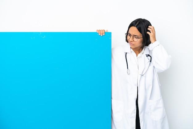 Junge gemischte ärztin mit einem großen plakat isoliert auf weißem hintergrund, die zweifel hat, während sie sich am kopf kratzt