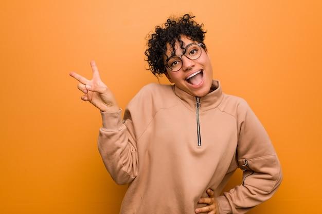 Junge gemischte afroamerikanerfrau gegen eine braune wand froh und sorglos, ein friedenssymbol mit den fingern zeigend.