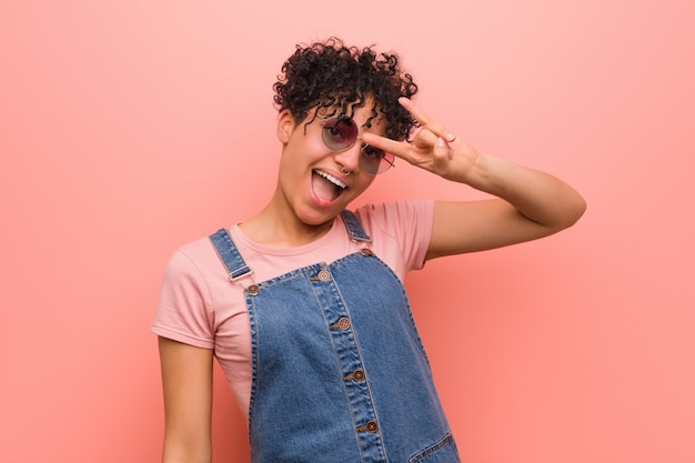 Junge gemischte afroamerikanerjugendlichfrau, die eine hörnergeste als revolutionskonzept zeigt.