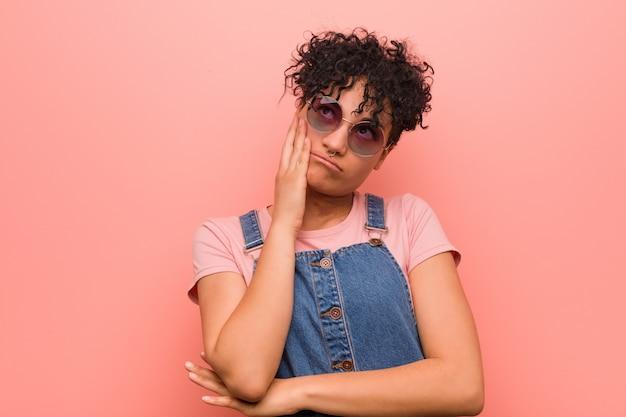 Junge gemischte afroamerikanerjugendlichfrau, die gelangweilt, ermüdet ist und einen entspannungstag benötigt.