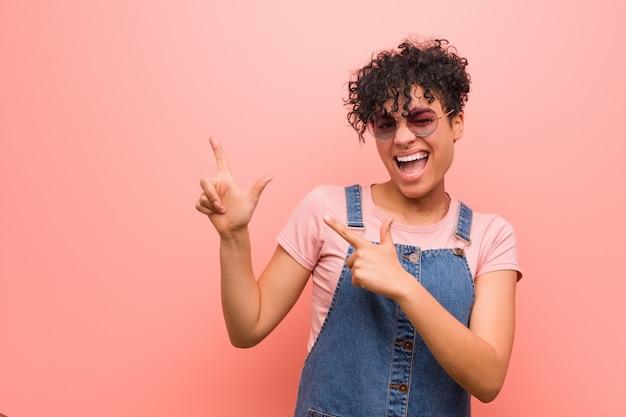 Junge gemischte afroamerikanerjugendlichfrau, die mit den zeigefingern auf einen kopienraum zeigt, aufregung und wunsch ausdrückt.