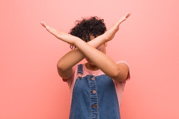 Junge gemischte afroamerikanische teenagerfrau, die zwei arme verschränkt hält