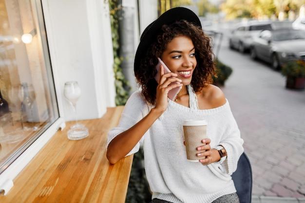 Junge gemischte frau mit afro-frisur, die durch handy spricht und im städtischen hintergrund lächelt. schwarzes mädchen, das freizeitkleidung trägt. tasse kaffee halten. schwarzer hut.