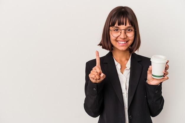 Junge gemischte geschäftsfrau, die einen kaffee hält, der auf dem weißen hintergrund lokalisiert wird, der nummer eins mit dem finger zeigt.