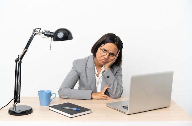 Junge, gemischte geschäftsfrau, die im büro mit einem ausdruck der frustration und des unverständnisses arbeitet