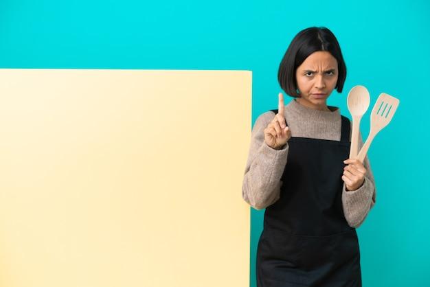 Junge gemischte kochfrau mit einem großen plakat isoliert auf blauem hintergrund, das eins mit ernstem ausdruck zählt