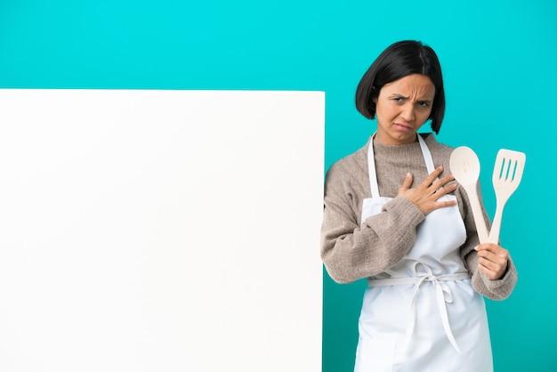 Junge gemischte köchin frau mit einem großen plakat auf blauem hintergrund mit schmerzen im herzen
